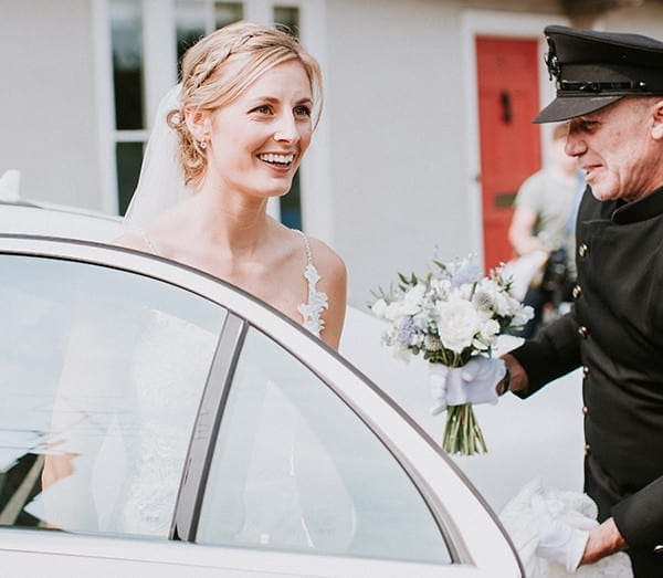 Perfect wedding car Chauffeur service in Suffolk, helping with wedding dress and flowers as she steps out of the Mercedes white wedding car. Perfect wedding day