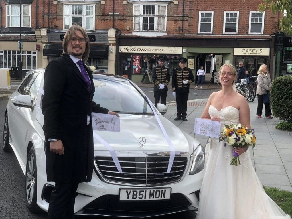 Newly weds with wedding car
